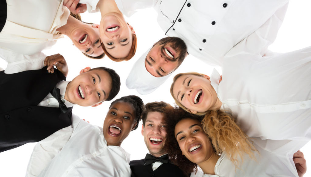Smiling Restaurant Staff Standing Against White Background